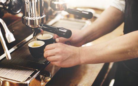 Das Bild zeigt einen Barista, der einen Espresso zubereitet.