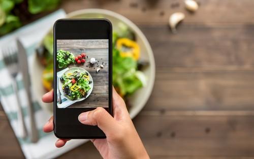 Jemand fotografiert sein Essen mit dem Smartphone.