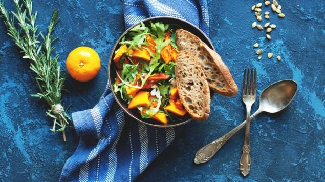 Schüssel Salat vor einem blauen Hintergrund