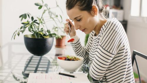Eine Frau schaut sich Notizen an und isst dabei.