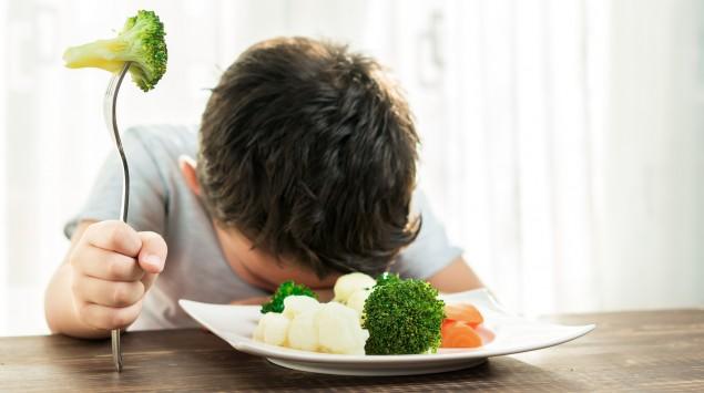 Ein Junge mag sein Gemüse nicht essen.