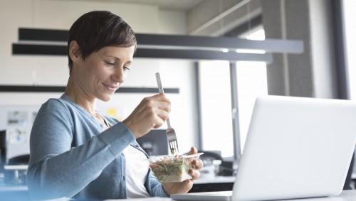 Eine am Schreitisch sitzende Frau isst einen Salat.