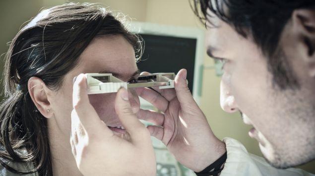 Eine Augenarzt untersucht die Augen einer Frau mit einem Exophthalmometer.