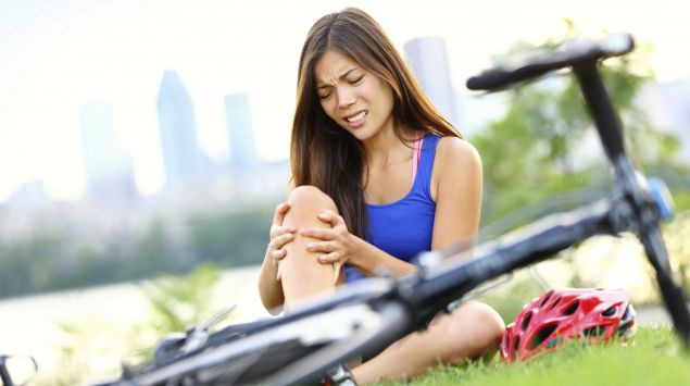 Eine Frau ist mit dem Fahrrad gestürzt und hält sich das schmerzende Bein.