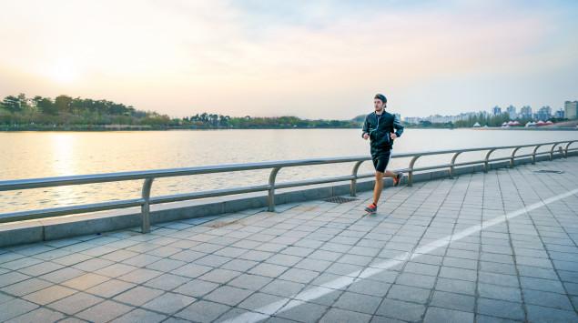 Ein Mann joggt einen Fluss entlang.