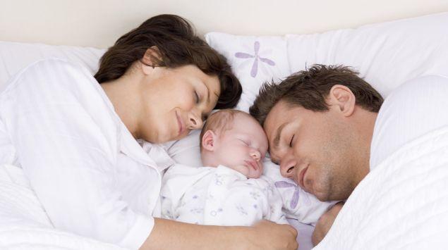 Mutter, Vater und Neugeborenes kuscheln im Bett
