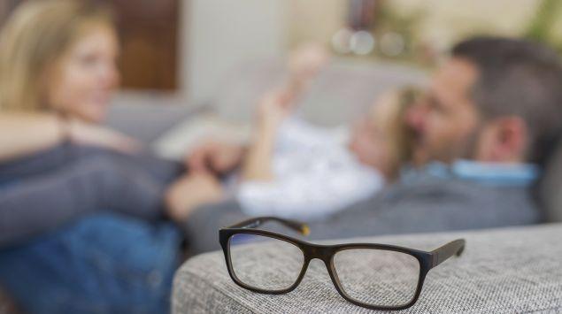 Eine Familie macht es sich auf einem Sofa gemütlich; auf der Armlehne liegt eine Brille.