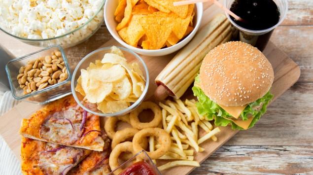 Man sieht ein Holzbrett mit verschiedenen Fast Food-Gerichten und Snacks sowie einen Becher Cola.