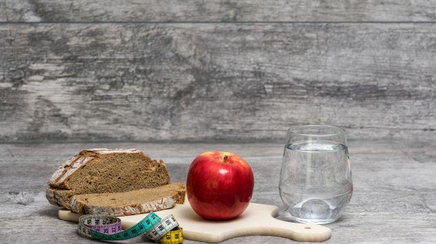 Holzbrett mit Wasserglas, Brot, Apfel und Maßband