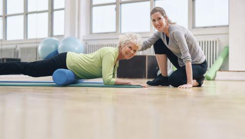 Das Bild zeigt eine ältere Dame, die mit einer Faszienrolle ihre Oberschenkelvorderseite trainiert.