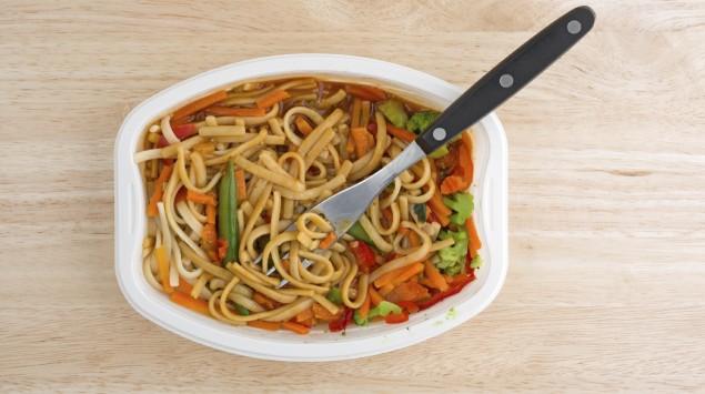 Auf einem Tisch steht eine Plastikschale mit einem Nudel-Gemüse-Fertiggericht.