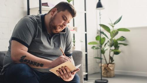 Ein übergewichtiger Mann trägt etwas in ein Buch ein.