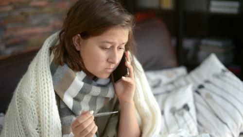 Eine Frau mit Fieber ruft beim Arzt an.