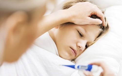 Jemand misst bei einem bettlägrigen Kind Fieber.
