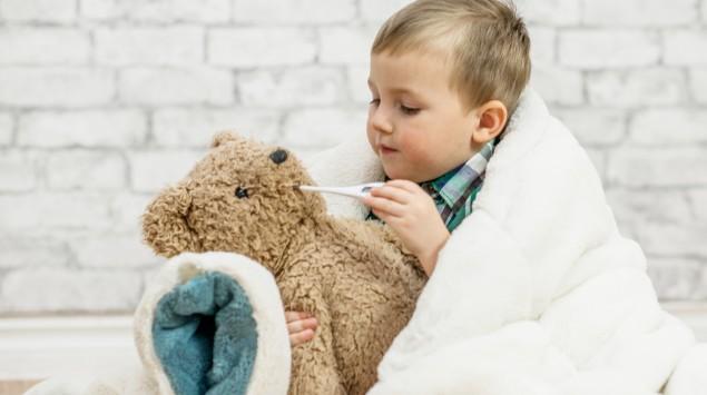Ein kleiner Junge misst beim Teddy Fieber.