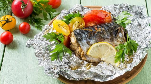 Auf einem Tisch steht ein Teller mit in Alufolie gebackenem Fisch, Tomaten, Zitronenscheiben und Petersilie.