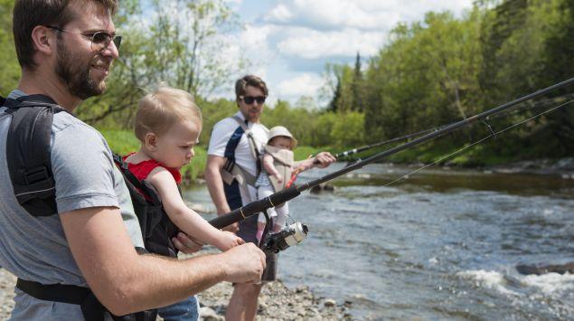 Väter mit Babys in der Trage angeln.