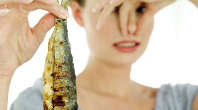 Eine Frau hält einen Fisch in die Luft und hält sich die Nase zu.