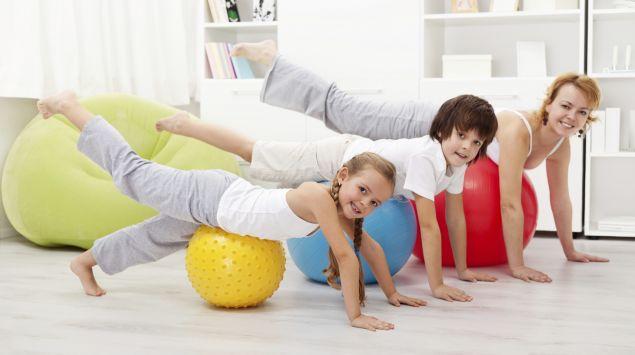 Frau, Junge und Mädchen turnen auf Gymnastikbällen.