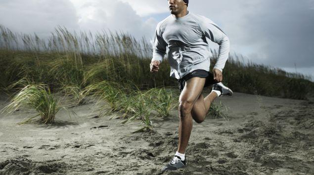 Das Bild zeigt einen sportlichen Mann, der durch den Sand läuft.