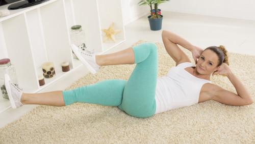 Eine Frau macht auf dem Boden Fitnessübungen.