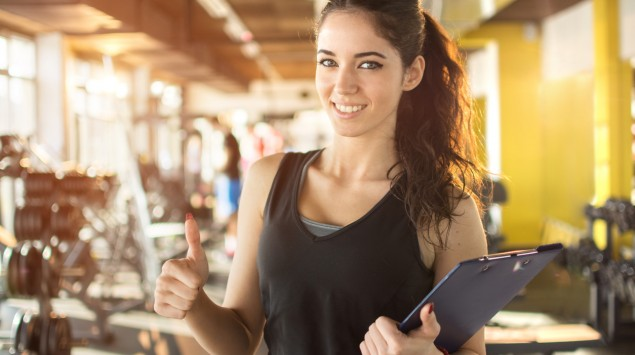 """Man sieht eine Frau in einem Fitnessstudio, die """"Daumen hoch"""" signalisiert."""