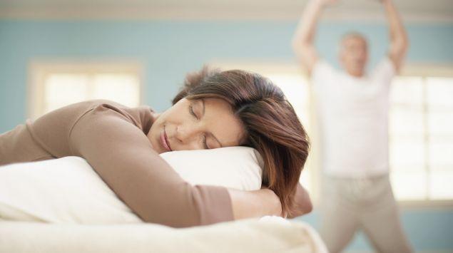 Eine Frau schläft auf dem Sofa, im Hintergrund macht ein Mann Sport