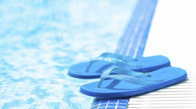 Das Bild zeigt ein Paar blaue Flipflops, die an einem Beckenrand in einem Schwimmbad stehen.
