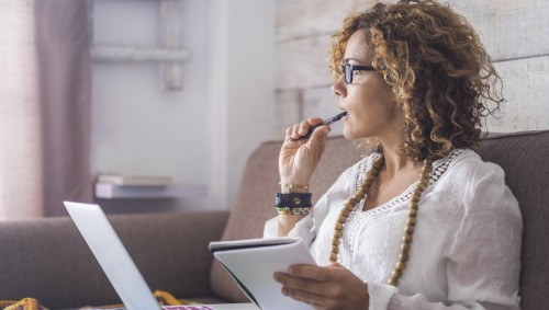 Eine Frau arbeitet konzentriert am Laptop.