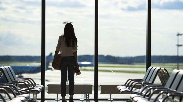 Eine Frau steht im Abflugbereich eines Flughafens und blickt durch das Fenster auf das Flugfeld.