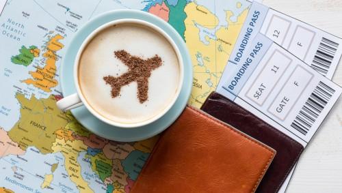 Man sieht eine Weltkarte, einen Cappuccino mit Flugzeug-Crema und Flugtickets.