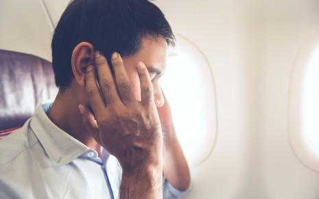 Druck auf den Ohren: Man sieht einen Mann im Flugzeug, der sich die Hände auf die Ohren drückt.