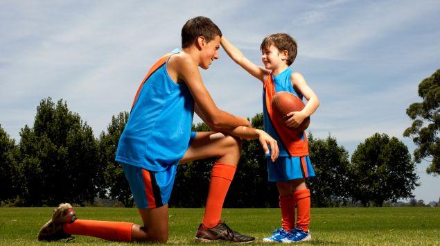 Das Bild zeigt ein Kind mit einem Football in der Hand.