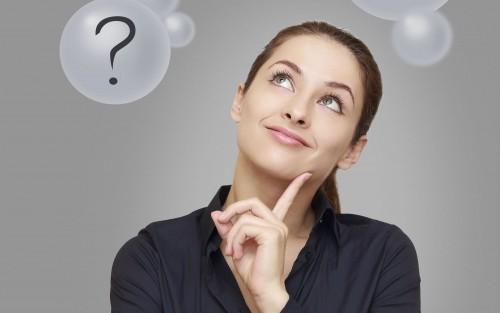 Eine Frau blickt nachdenklich nach oben, über ihr sieht man Luftblasen mit Fragezeichen.