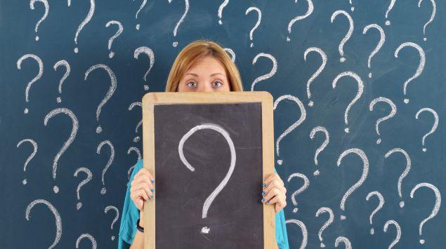 Eine Frau steht vor einer Tafel mit Fragezeichen.