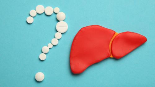 Fragezeichen aus weißen Tabletten neben einem roten Lebermodell auf blauem Grund