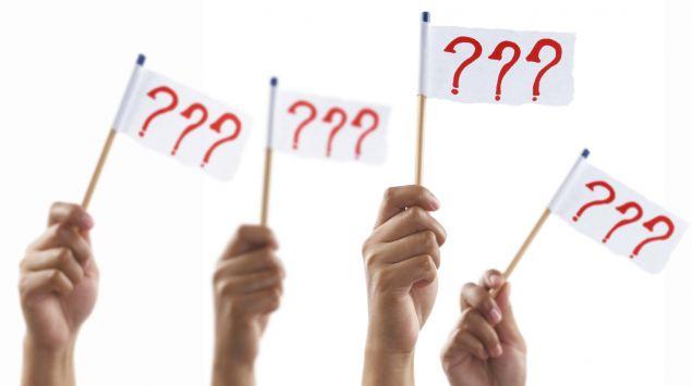 Mehrere Hände halten Fähnchen mit Fragezeichen hoch.