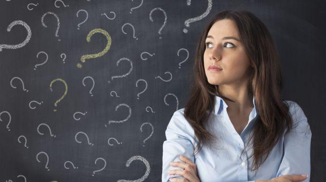 Eine Frau lehnt an einer Tafel mit Fragezeichen.