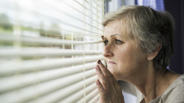 Eine ältere Frau späht durch die Jalousie.