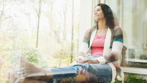 Eine Frau sitzt entspannt am offenen Fenster.