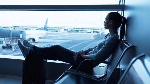 Eine Frau sitzt im Flughafenterminal mit Blick auf das Vorfeld auf einer Bank und hat ihre Füße auf einem Koffer abgelengt.