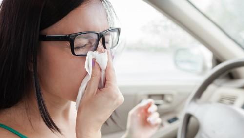 Eine junge Frau am Steuer eines Autos putzt sich die Nase.