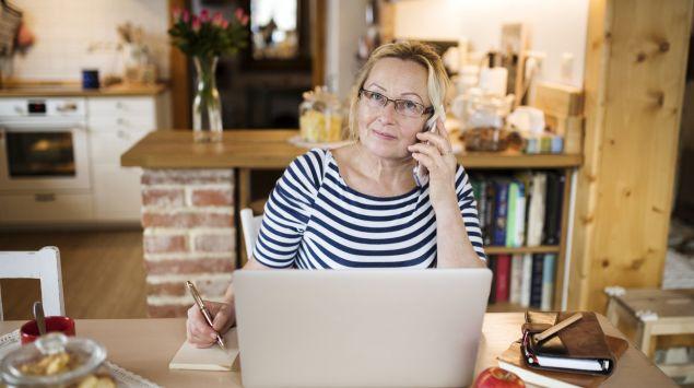 Eine Frau mittleren Alters am Telefon.