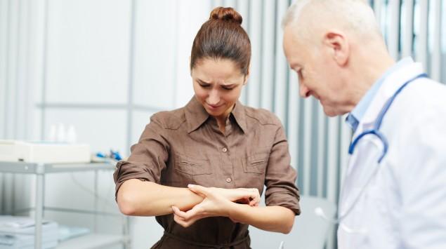 Eine Patientin zeigt dem Arzt ihren Arm.