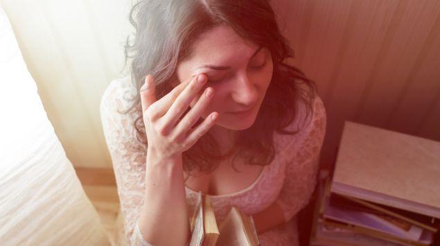 Eine Frau berührt mit dem Zeigefinger ihr Augenlid.