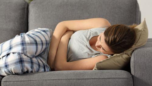 Eine Frau liegt mit Bauchkrämpfen auf dem Sofa.