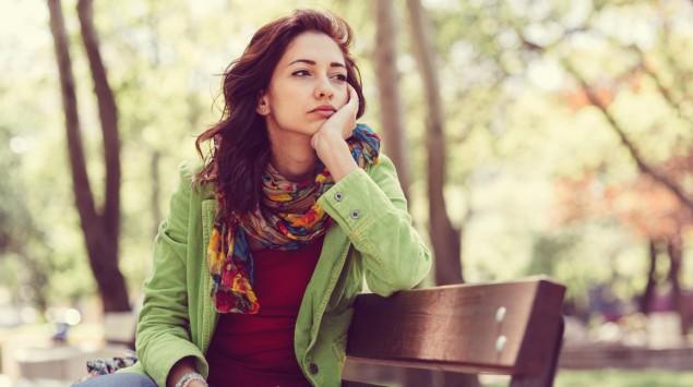 Eine bedrückt wirkende Frau sitzt auf einer Bank im Park.