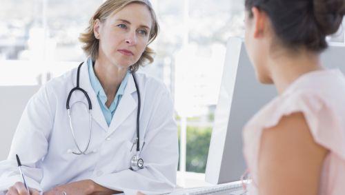Eine junge Frau in der Sprechstunde bei einer Ärztin.