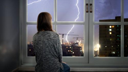 Eine Frau schaut bei Gewitter aus dem Fenster.