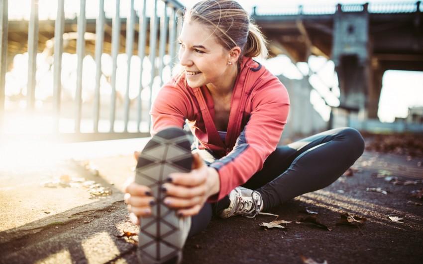 Immunsystem stärken: Eine Frau hält sich Herbstlaub vor das Gesicht.